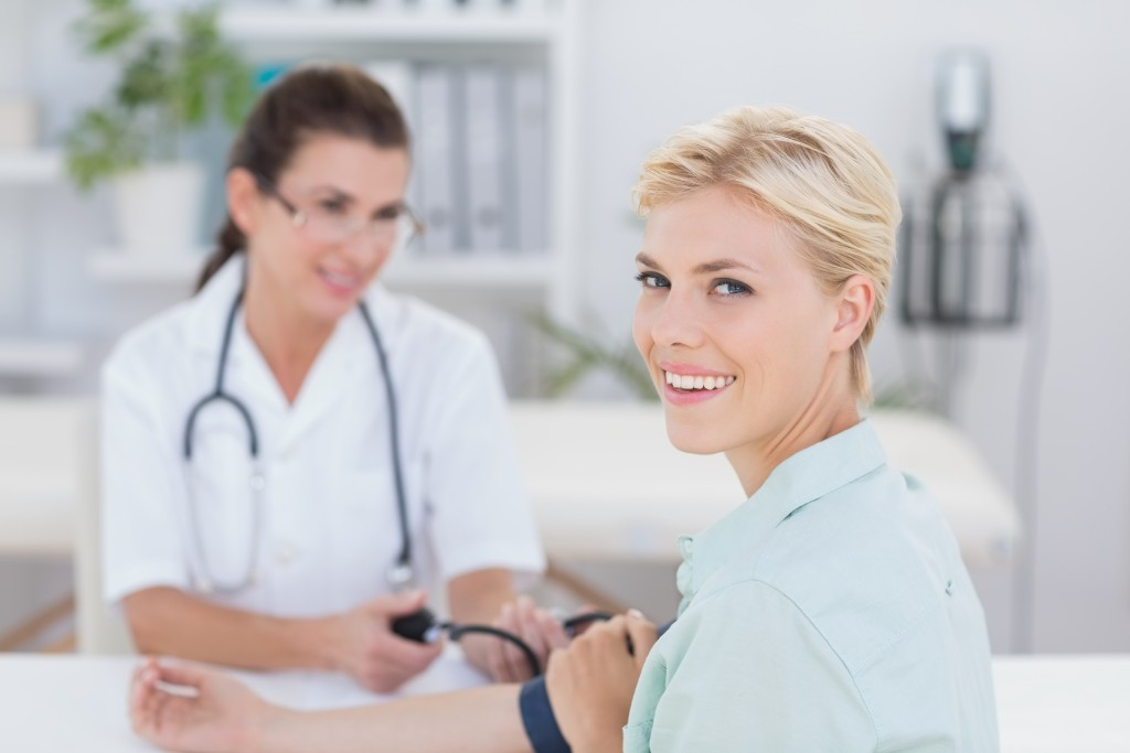 Doctor taking blood pressure of her smiling patient